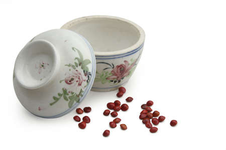 sculpt: Traditional Chinese covered top soup bowl with spread of red seed.