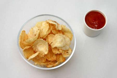 accompagnement: Vue de dessus d'un bol en verre avec d'arrow-root chips avec un petit pot de sauce chili-accompagnement