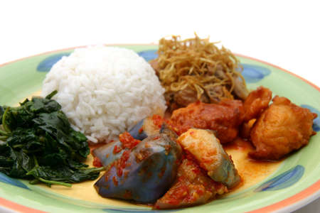 A colorful plate of rice, vegetables and chicken portions for dinner photo