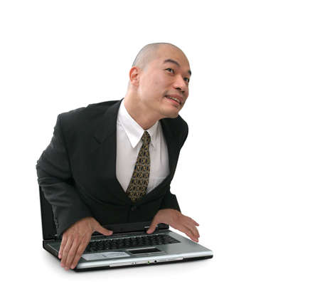 cramped: Oriental man in suit climbing out of a cramped laptop computer