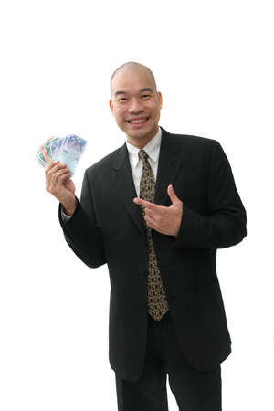 punhado: Happy oriental business man in suit pointing at a handful of money
