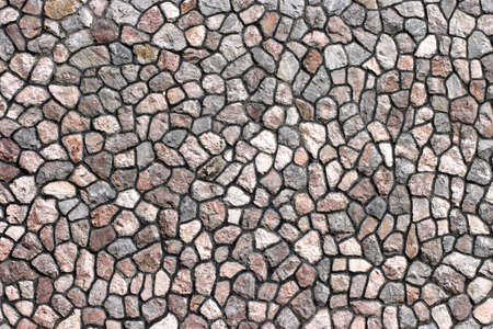 unpolished: Granite stone wall with uneven stones Stock Photo