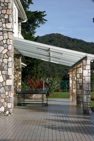 Een open veranda aan de achterkant van een bungalow met een grote achtertuin Stockfoto - 369452