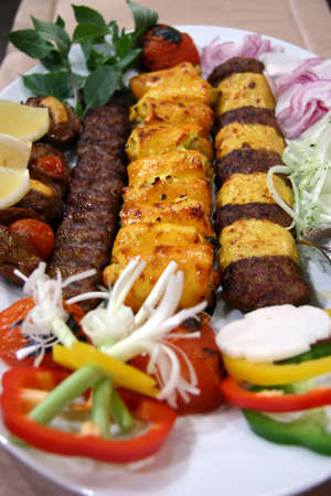 browned: Long strips of lamb and chicken kebabs with relish, slice onions, turnip, capsicum, mint leaves and lemon wedges