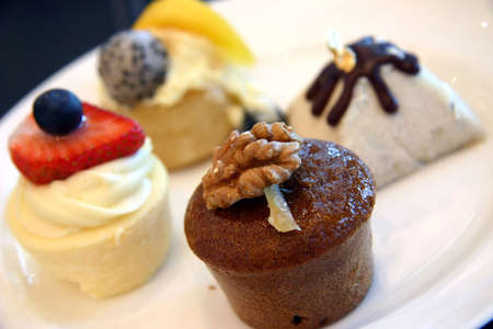 Small servings of varied desserts on offering photo