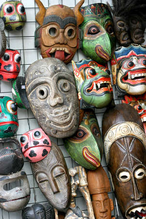 memorabilia: A variety of carved and painted wooden masks hanging on the wall of a store