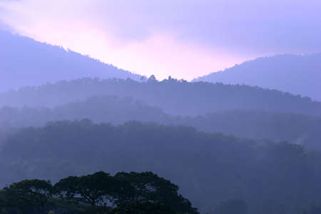 hued: Purple hued hills and mountains on a semi foggy day