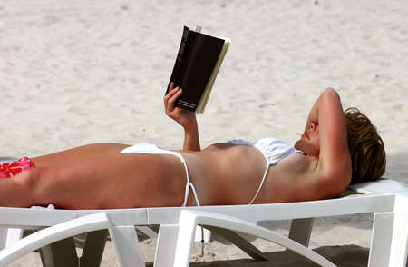 Woman reading a book sunbathing on the beach photo