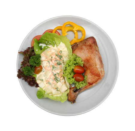 Roasted leg of chicken with potato salad, capsicum slices and cherry tomatoes photo
