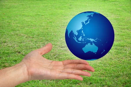 australasia: Hand holding a the world with a green grassy field in the bckground