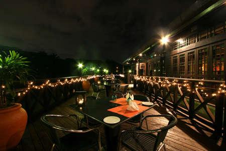 Night time on a verandah at a lake-side bar at a Kuala Lumpur resort hotel photo