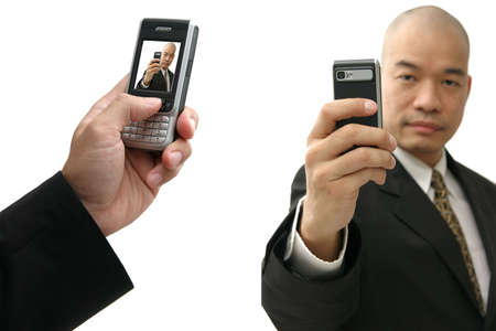 Oriental man in suit holding up a camera-phone with confidence photo