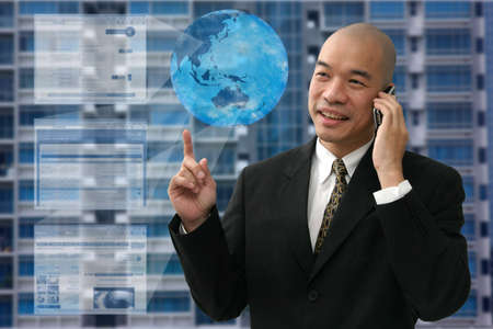 Oriental man in suit with great ideas on cell phone looking happy. photo