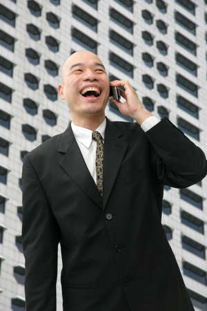 Oriental man in suit on cell phone looking happy and laughing. photo