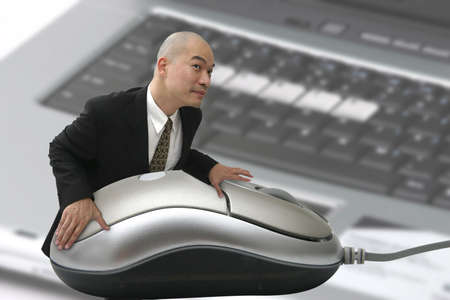 Man with giant mouse and computer in background Stock Photo - 509130