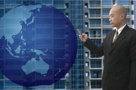 Chinese business man on a cellular phone with building in background and globe in front of him photo