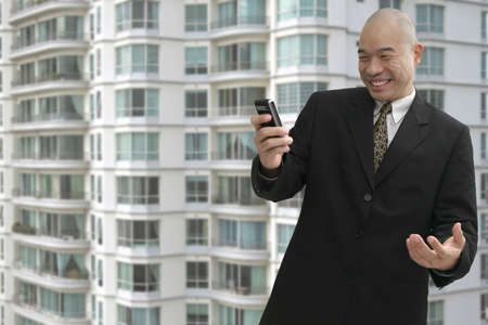 Chinese business man on a cellular phone with building in background photo
