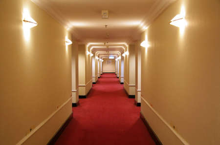 Long hotel corridor with red carpet and yellow wallpaper photo