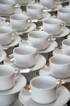stirrer: Stacks of coffee cups on saucers with silver teaspoons
