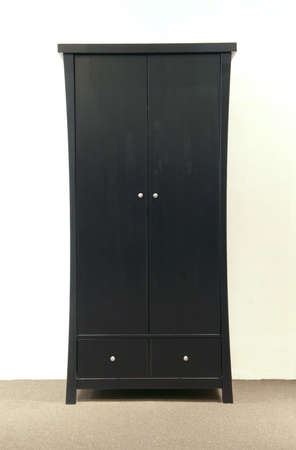 to lacquer: Slim and tall dark lacquer wardrobe with two doors and drawers Stock Photo