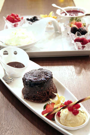 Moist chocolate cake with rich chocolate sauce and a scoop of vanilla ice-cream photo