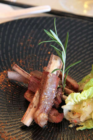 Roasted cuisine lamb ribs with lettuce leaves on a unique stone-black spiral plate photo