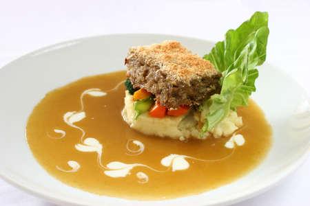 Gourmet meatloaf en una cama de verduras y caldos adornado con lechuga recortada