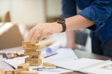 close up engineering man hand playing wood block game for building tower in office room , success goal concept
