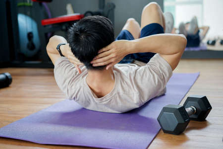 close up rear view on young man in sit-up pattern workout on exercise mat at home gym in the morning for quarantine and lifestyle and healthy concept Фото со стока