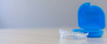 close up dental aligner retainer (invisible) on dentist's table office background for teeth treatment course concept