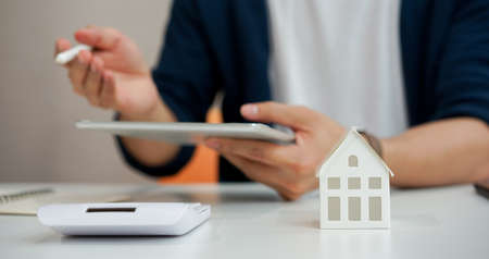 close up house model with salesman holding tablet and explaining to customer about how to refinance and how to insurance cover at bank office workplace for mortgage financial concept Standard-Bild