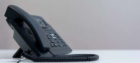 close up telephone VOIP technology standing on office desk in office room for contacting with colleagues , partner or vendor and network operation center job concept