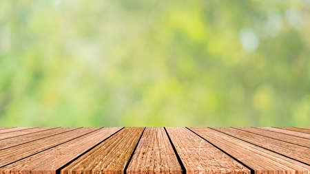 blur nature panoramic background with glow sunny light and aged plain wood table top perspective view for promote product concept. Stockfoto