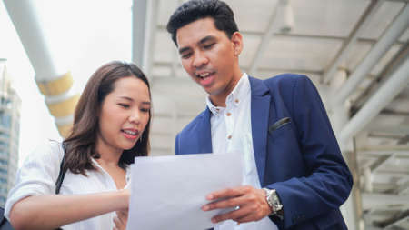 close up businesswoman explaining and brief detail of company's marketing research report on tablet to businessman before go to join meeting conference event , new business and startup concept Imagens