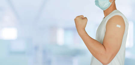 pack of young asian man with protective face mask sand showing bandage on shoulder to expression after antibody vaccinated isolated on blur hospital background for health concept