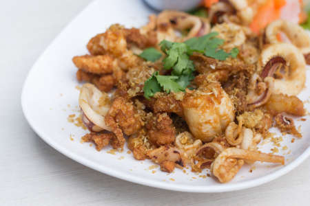 Fried squid with garlic in white dish on the table. Stock Photo