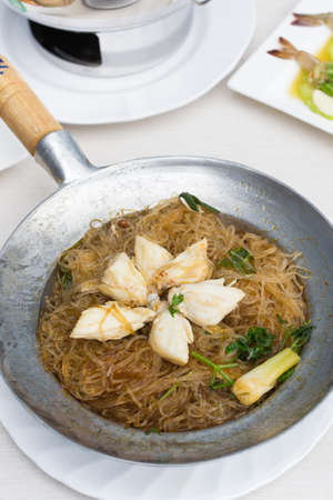 Crab with vermicelli in stainless bowl on the table.