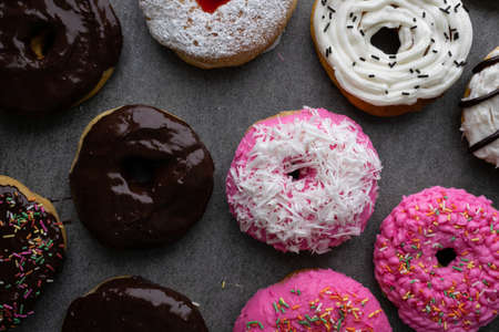 Donut with chocolate glazed and strawberry glazed on concrete table.