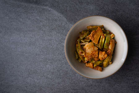 Spicy fried three layer pork with lentils in gray bowl on the concrete table background. Imagens