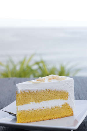 Cream butter cake in white dish on wooden table with sea background.