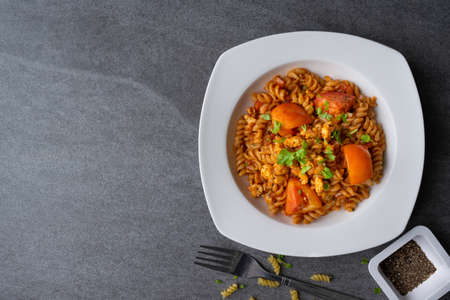 Spiral pasta in sauce tomato with chicken in white dish on concrete table.