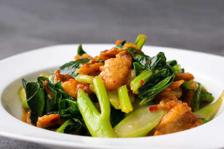 Fried Chinese kale with crispy skin chicken in oyster sauce and chilli in the white dish. Banco de Imagens