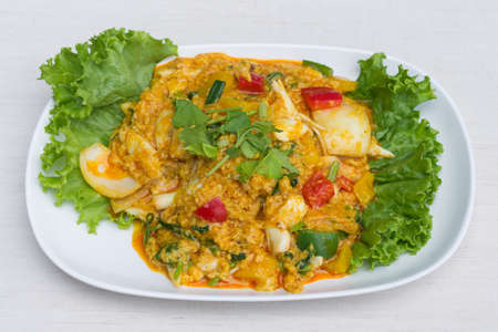 Fried crab with curry powder in white dish on the table.