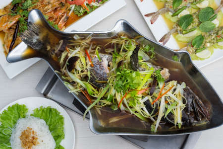 Steamed grouper with soy sauce in fish shape pot on the table with other food. Stock Photo