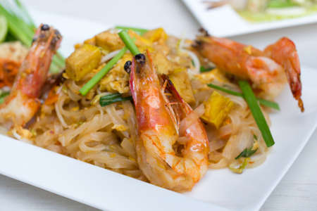 stir-fried rice noodles with fresh shrimp and tofu(Pad Thai),in white dish.