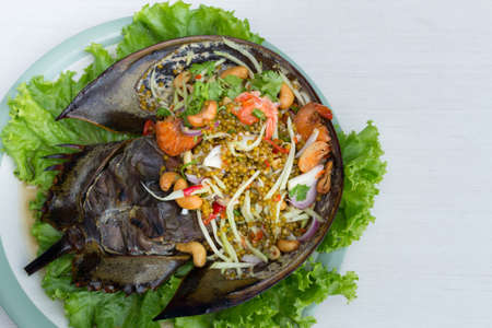 Spicy salad horseshoe crab egg with lettuce in white dish on table. 免版税图像