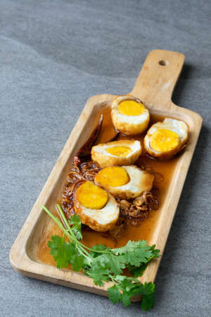 Boiled and Fried eggs in sweet and sour sauce with coriander in the wooden dish on table.
