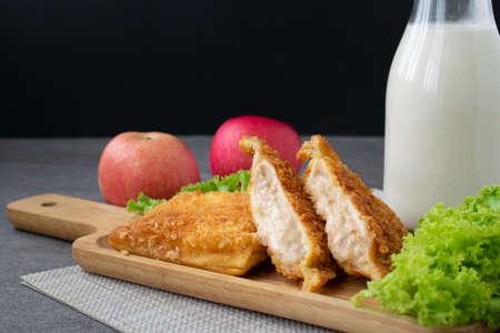 Deep fried sandwich stuffed tuna in wooden dish on table.