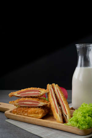 Deep fried sandwich stuffed ham cheese in wooden dish on table.