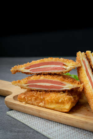 Deep fried sandwich stuffed ham cheese in wooden dish on table. Stock Photo